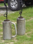 Two drip torches sit ready to start the fire.  The tank holds a mix of diesel and gasoline.  The tip is lit and when tipped downward the torch drops flaming bits of fuel.  This tool is used to spread the fire during a prescribed burn.