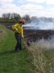 Emily works with a broom to put the fire out at the edges